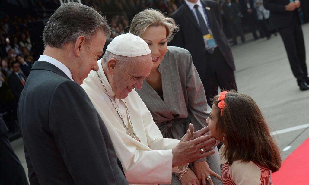 Una niña recibe el caluroso saludo del Papa Francisco, en el inicio de su histórica Visita Apostólica. Lo acompañan el Presidente Juan Manuel Santos y su esposa, María Clemencia Rodríguez. (Dar clic para ampliar).