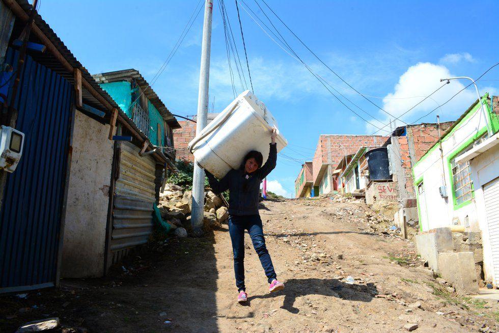 Jessica Hernández carga con una lavadora para alquilarla en Soacha, cerca de Bogotá (Colombia). Foto Pablo Lalide